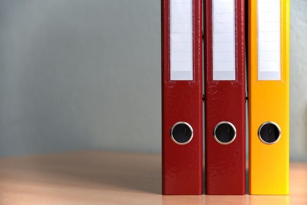 オフィスのテーブルの上の文書用の大きなカラーフォルダー、クローズアップ、コピースペース