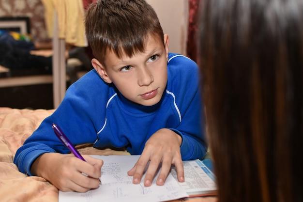 夜のベッドの上の部屋で母親と学校の宿題をしている十代の少年