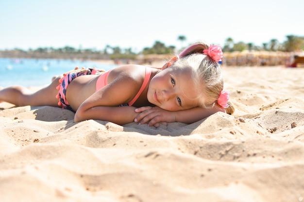 女の子は海と日光浴の近くのビーチの砂の上にあります。
