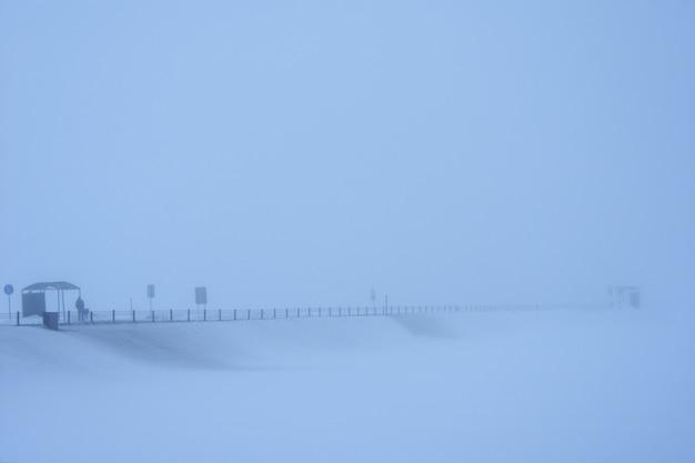 男は霧の中で雪に覆われた道で輸送を待っています