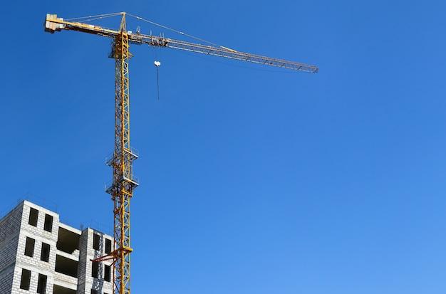Желтый башенный кран при строительстве дома на фоне голубого неба