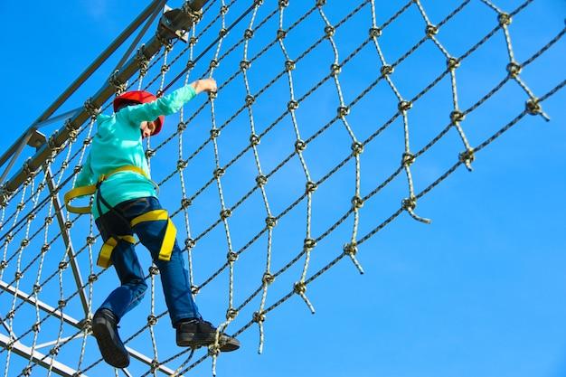 Мальчик-подросток двигает вертикальную сетку по полосе препятствий в парке развлечений
