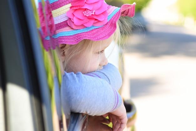 女の子が乗っている間車の窓の外に見える