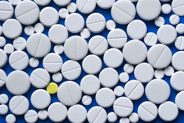 黄色と白の錠剤が青い医療テーブルの上に散らばって