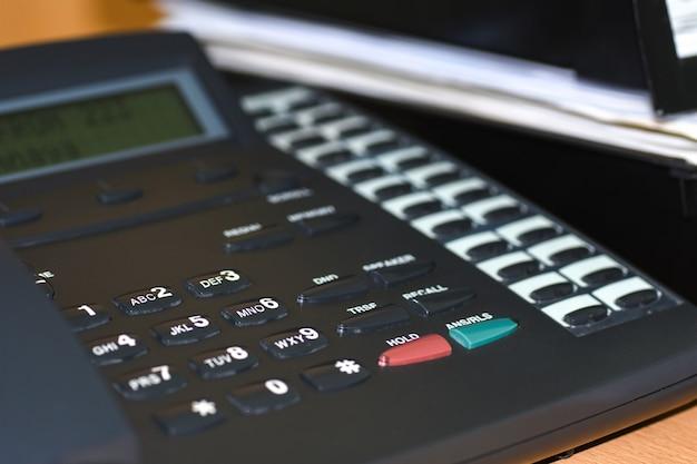 ボタンとディスプレイのオフィスの机の上の黒い線電話