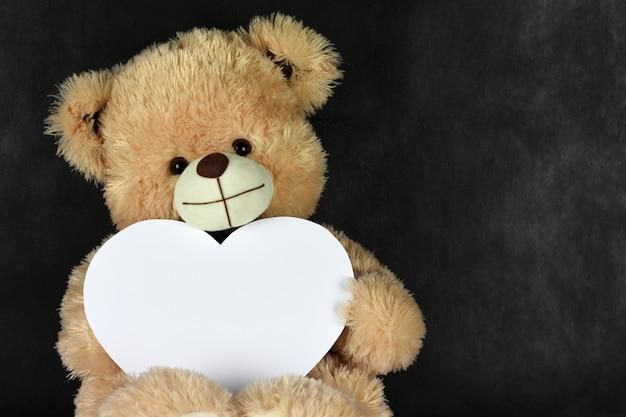 Медведь тедди с рамкой в форме сердца любит тебя в день святого валентина