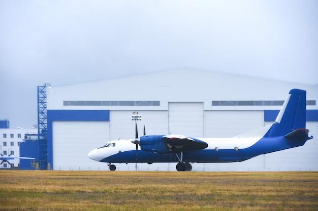 Бизнес-самолет покидает авиационный бокс на взлетно-посадочной полосе аэропорта в пасмурную погоду с дождем