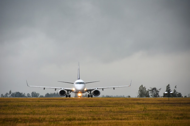 Пассажирский самолет с включенными огнями вылетит на взлетно-посадочную полосу в поле аэропорта вечером под дождем