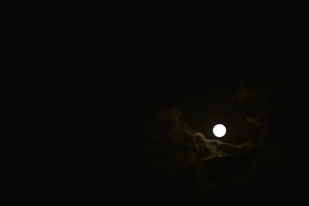 夜空に浮かぶ雲を通して月が輝く