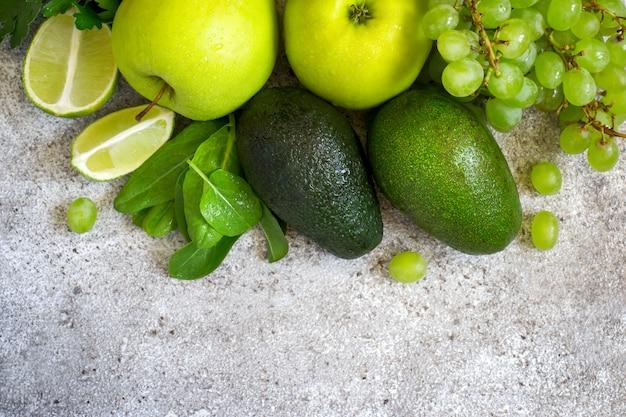 灰色のコンクリート表面の緑の野菜と果物の選択
