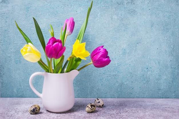 白い花瓶のチューリップと水仙の春の花束