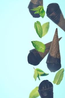 Черное мороженое в вафельных рожках на пастельном фоне