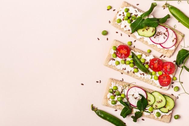 Здоровые бутерброды с мягким сыром и сырыми овощами на хрустящем хлебе.