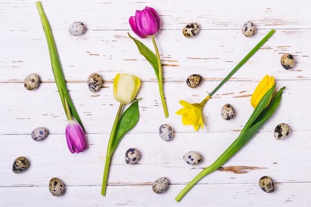 イースター春の花の背景。色とりどりの花と白い木の板にウズラの卵