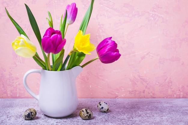 白い花瓶のチューリップと水仙の春の花束。イースターのグリーティングカード