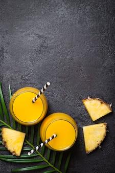 Ананасовый сок или смузи и ломтики ананаса на черном фоне