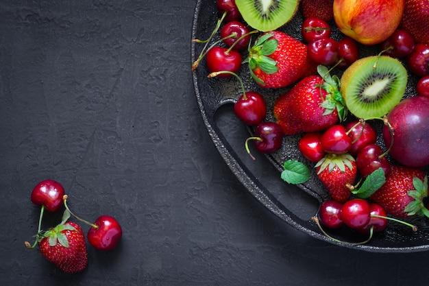 Микс из летних ягод и фруктов на черной тарелке.