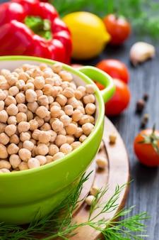 カラフルな野菜の背景に乾燥ひよこ豆とボウルします。