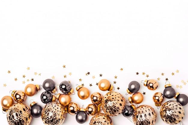 クリスマスホワイトバックグラウンド。輝くゴールドとグレーのボールと紙吹雪の境界線