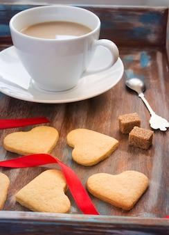 Деревянный поднос с чашкой кофе и печеньем в форме он