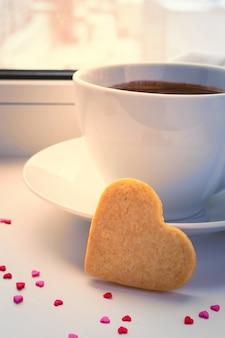 冬の窓辺でコーヒーの朝のカップ。クッキーの心。ロマンチックなバレンタインデー