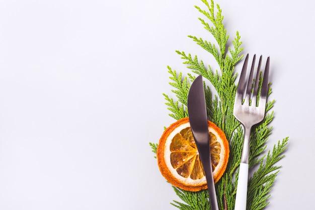 Рождественская сервировка. вилка и нож украшены хвойной веточкой и долькой апельсина