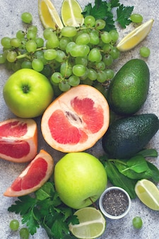 Выбор зеленых овощей и фруктов на серой бетонной спине