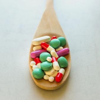 Много таблетки и витамины в деревянной ложкой на светлом фоне.