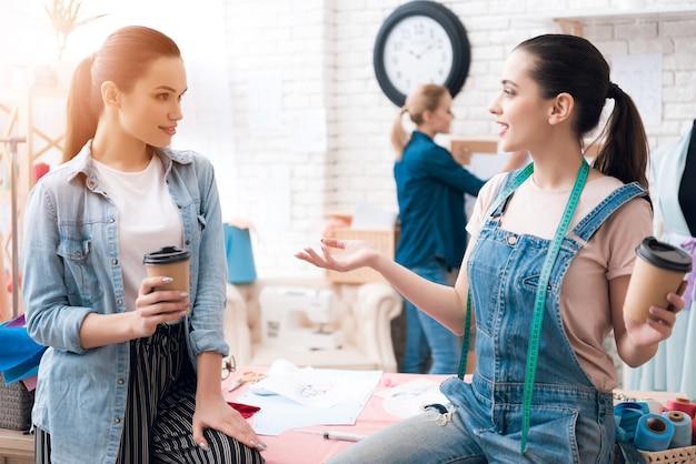 女の子はコーヒーを飲みながら話し、腕を振っている。