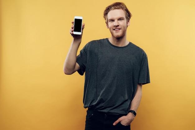 ハンサムな男が服を着て、スマートフォンを提示します。