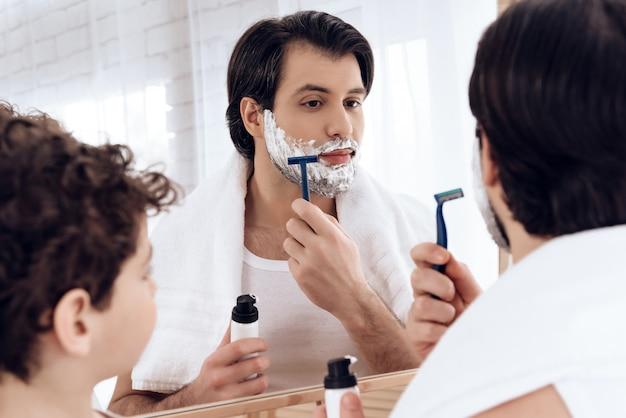 息子が見ている間、お父さんは慎重に剃ります。
