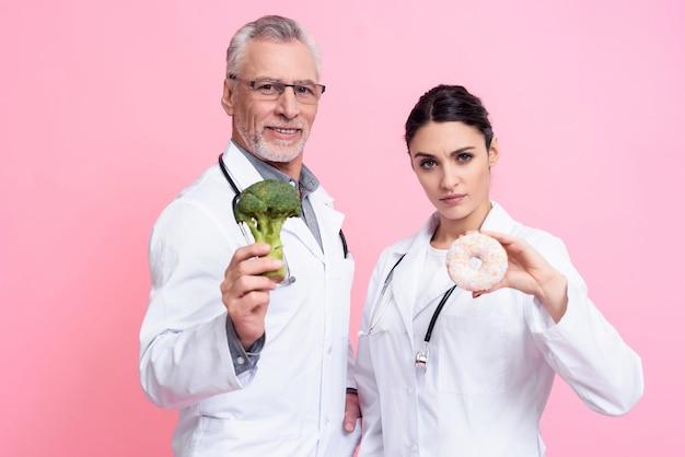 医師はブロッコリーとドーナツを抱えています。