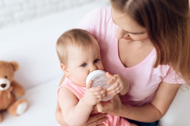 Молодая мать кормления ребенка бутылку молока домой.