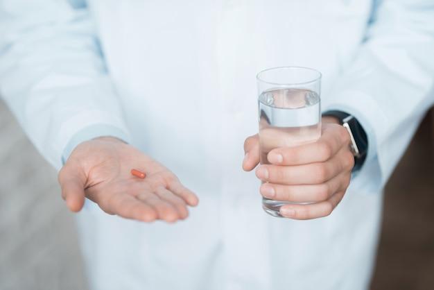 閉じる。医者は赤い錠剤とコップ一杯の水を保持しています。