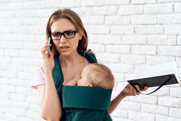 ビジネスの女性が電話を話して新生児を保持しています。