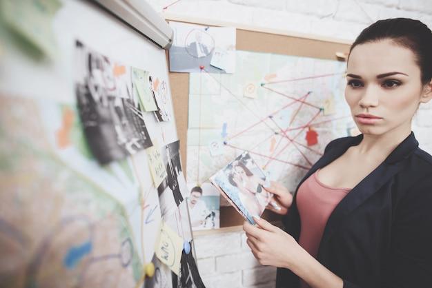 女性は、オフィスの手がかりマップに写真を入れています。