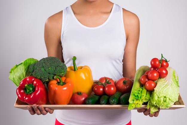 Черная девушка держа поднос с овощами изолированный.