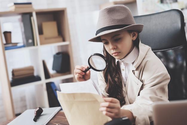 小さな女の子は写真を見て机に座っています。