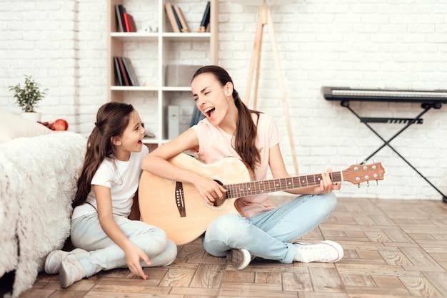 ママと彼女の娘は床に座って笑っています