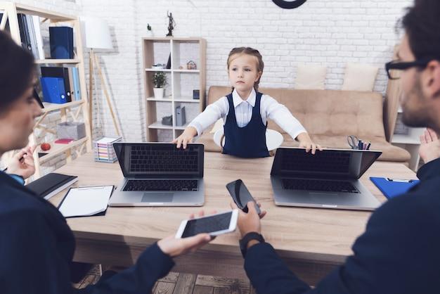 Маленькая девочка закрывает ноутбук для родителей.
