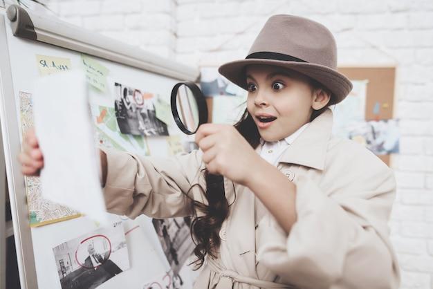 小さな女の子は、手がかりボードの近くの写真を見ています。