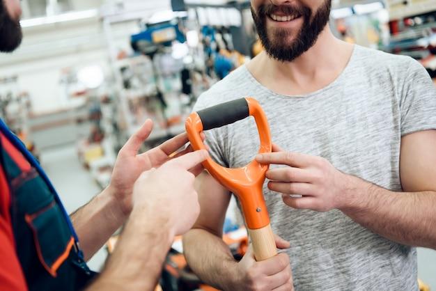 売り手は新しいシャベルのハンドルを見せる。