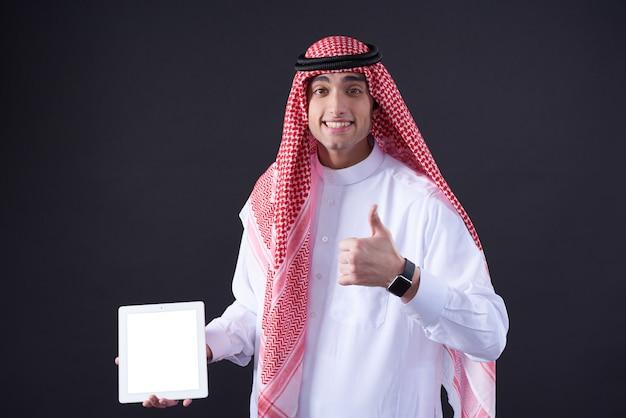 中東の男が分離した白いタブレットでポーズします。