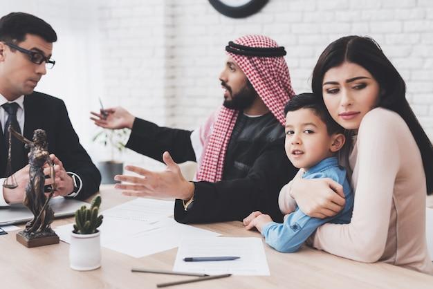 Мужчина заполняет документы о разводе, женщина держит сына.