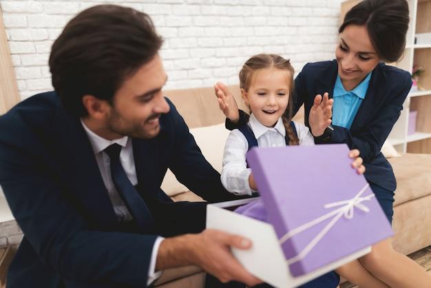 Папа открывает красивый подарок для маленькой дочери.
