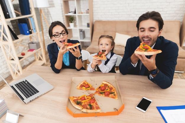 Молодая семья бизнесменов обедает дома.