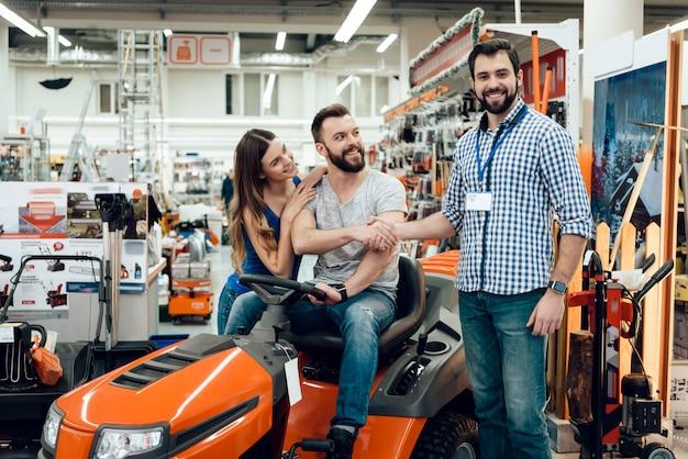 Продавец показывает уборочную машину клиентам
