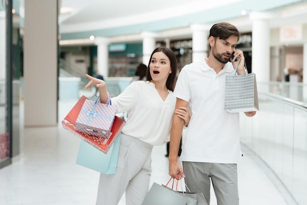 女性は店に行きたいのですが、男性は電話で話しているのに忙しいです。