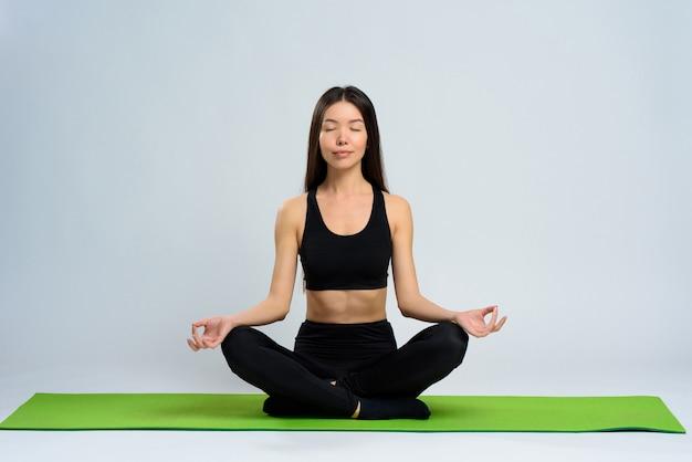 アジアの女の子はジムカーペットについて瞑想します。ロータスポーズ