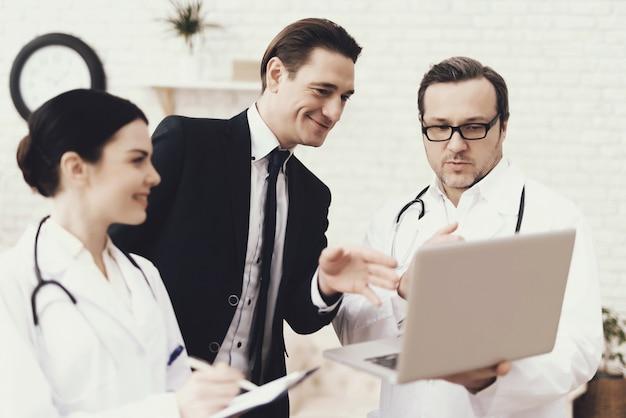 経験豊富な医師がラップトップの結果を表示します。